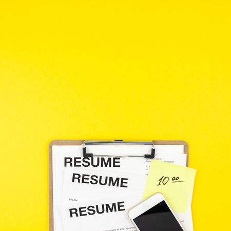 Creative top view flat lay of desk with resume documents copy space on bold yellow background in minimal style. Concept of new job, hiring recruitment process, new team members screening