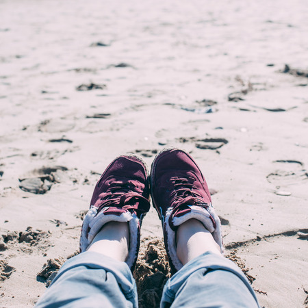 Feet of young woman in sport footwear and jeans relaxing after hiking on sand beach. Square POV. Adventure concept backdrop for motivational quotes, blog posts, your text. Toned image