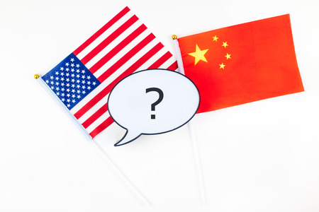 Creative top view flat lay of China and USA flag bubble lightbox with question mark and copy space white background in minimal style. Concept of trade war between USA and China