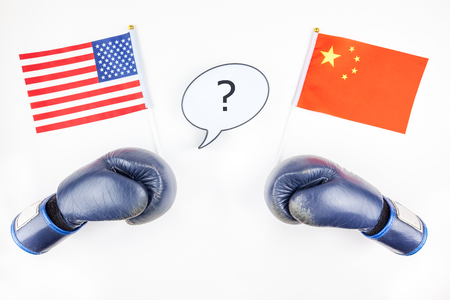 Creative top view flat lay of Two boxing gloves with China and USA flag bubble lightbox with question mark and copy space white background in minimal style. Concept of trade war between USA and China 版權商用圖片