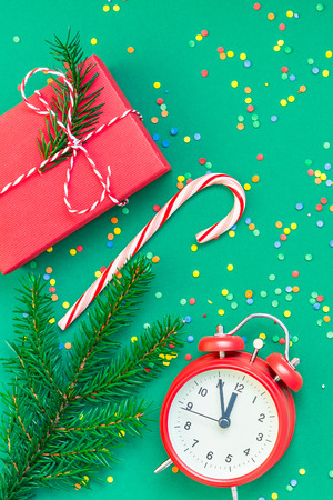 New Year or Christmas pattern flat lay top view with red alarm clock twelve midnight fir tree branch Xmas holiday celebration green paper bright colorful confetti background. Template text design 2019