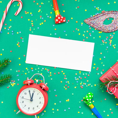 New Year or Christmas mock up flat lay top view with red alarm clock twelve midnight fir tree branch Xmas holiday celebration green paper bright colorful confetti background. Square Mockup text 2019 Stock Photo