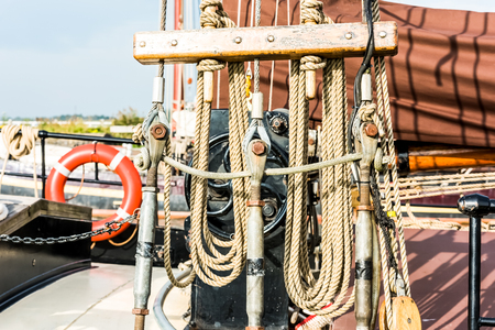Recreational yacht detail with ropes and other equipment. Filtered shot with sun reflection in background 版權商用圖片