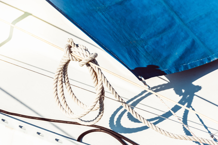 Recreational yacht detail with ropes and other equipment. Filtered shot with sun reflection in background Reklamní fotografie