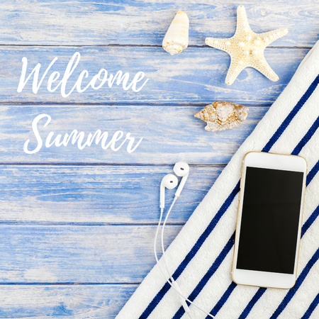 Square Creative flat lay concept of summer travel vacations. Top view of beach towel smartphone seashells starfish on pastel blue wooden planks background with Welcome summer text Reklamní fotografie