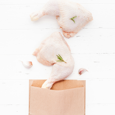 Creative Top view flat lay of fresh raw chicken legs with rosemary herbs garlic tomatoes on white wooden background with copy space. Food preparation recipe cooking concept