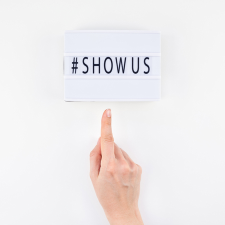 Creative top view flat lay of lightbox with hashtag Show Us message white background minimal style. Concept of Project world largest stock photo collection created by women