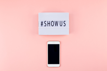 Creative top view flat lay of lightbox with hashtag Show Us message and mobile phone mockup pink background minimal style. Concept of Project world largest stock photo collection created by women
