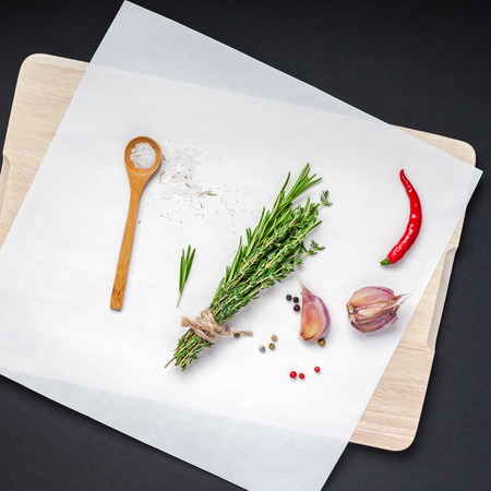 Flat lay overhead top view of greens herbs and spices on wooden cutting board on black background with copy space. Menu frame design food background with cooking ingredients