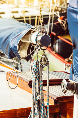 Recreational yacht detail with ropes and other equipment. Filtered shot with sun reflection in background Фото со стока