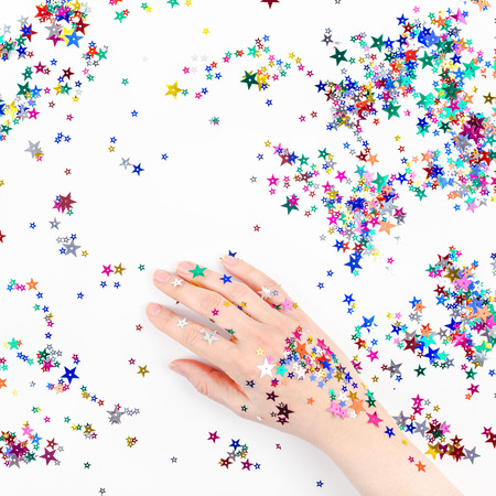 Bright festive color confetti star sparkles with woman hand on white background. Creative conceptual Christmas holiday birthday party top view flat lay backdrop for your blog, text or design