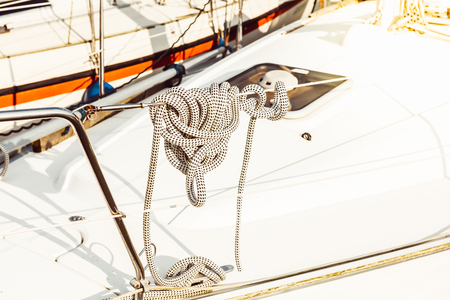 Recreational yacht detail with ropes and other equipment. Filtered shot with sun reflection in background Фото со стока - 124608570