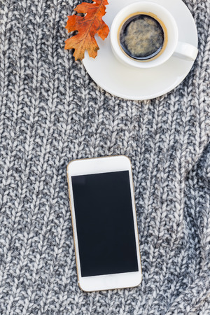 Creative autumn flat lay overhead top view stylish home workspace with smartphone notebook coffee cup cozy gray knitted plaid background copy space. Fall season template for feminine blog social media