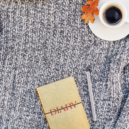 Creative square autumn flat lay overhead top view stylish home workspace with notebook coffee cup cozy gray knitted plaid background copy space. Fall season template for feminine blog social media Stock Photo