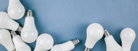 Energy-saving and eco-friendly life in conceptual frame pattern. Creative top view flat lay of LED light bulbs composition with copy space on blue background in minimal style. Standard-Bild - 124855270