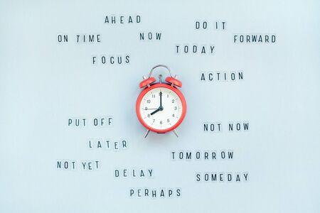 Vista superior creativa plana del reloj de alarma con mensajes sobre el retraso o comenzar a hacer la tarea copia espacio fondo azul estilo minimalista. Concepto de procrastinación, gestión del tiempo en los negocios y la vida.