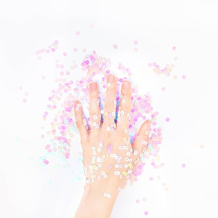 Pearl pastel confetti sparkles with woman hand on white background. Creative conceptual top view flat lay backdrop for your blog, text or design Archivio Fotografico