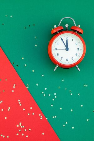 New Year or Christmas pattern flat lay top view with alarm clock twelve midnight Xmas holiday celebration red green paper golden sparkles confetti background. Template for your text design 2020 Stock Photo
