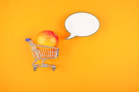 Mango fruit in shopping cart in creative conceptual top view flat lay composition with blank lightbox bubble mock up isolated on bold color background in minimal style with copy space. Pop art poster