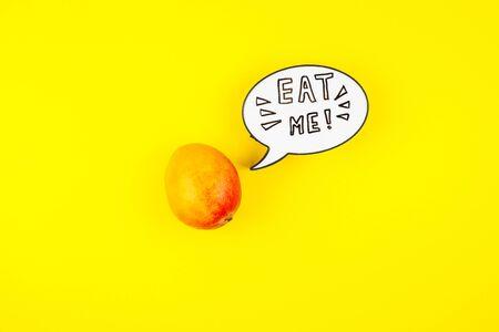 Fruta de mango en la composición laica creativa conceptual superior vista plana con burbuja de caja de luz con lema escrito a mano Eat me aislado sobre fondo de color negrita en estilo minimalista con espacio de copia. Cartel de arte pop Foto de archivo