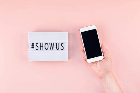 Creative top view flat lay of lightbox with hashtag Show Us message and mobile phone in hand mockup pink background minimal style. Concept Project world largest stock photo collection created by women