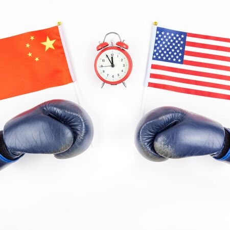Creative top view flat lay of Two boxing gloves with China and USA flag red alarm clock and copy space on white background in minimal style. Concept of trade war between USA and China