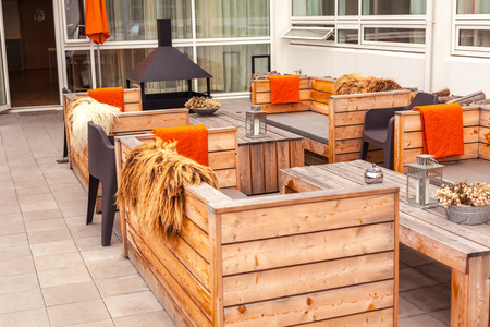 Outdoor restaurant terrace with wooden furniture in scandinavian style. Eco-friendly authentic design. Éditoriale