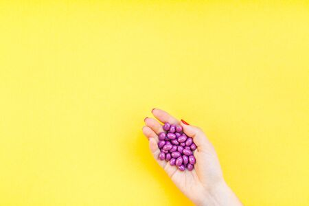 Woman hand holding purple pills handful isolated on bold yellow background with copy space. Template for feminine beauty blog social media. Female healthcare or suicide prevention concept