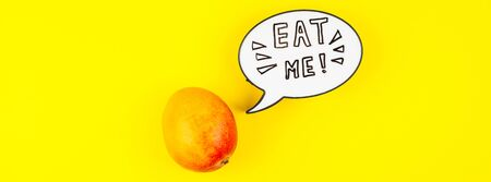 Mango fruit in creative conceptual top view flat lay composition with lightbox bubble with Eat me handwritten slogan isolated on bold color background in minimal style with copy space. Pop art poster Foto de archivo