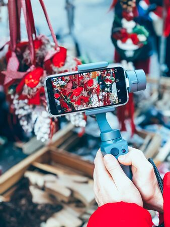 GERMANY, NUREMBERG - DECEMBER 17, 2018: Close-up of man blogger hands shooting video on smartphone IPhoneXS using an image stabilizer DJI Osmo Mobile on the Christmas market in Nuremberg Editorial