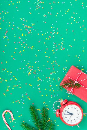 New Year or Christmas pattern flat lay top view with red alarm clock twelve midnight fir tree branch Xmas holiday celebration green paper bright colorful confetti background. Template text design 2020