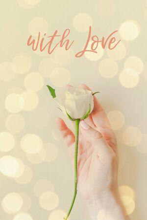 Mano creativa della donna della cartolina di vista superiore che tiene la rosa bianca fresca, testo con amore su fondo di carta pastello con bokeh. Biglietto d'invito matrimonio modello cartolina vacanza holiday