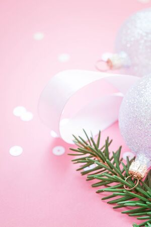 New Year Christmas Xmas holiday celebration composition pearl decorative toy balls green fir branch sparkles confetti pink paper background copy space Template frame for greeting postcard text design