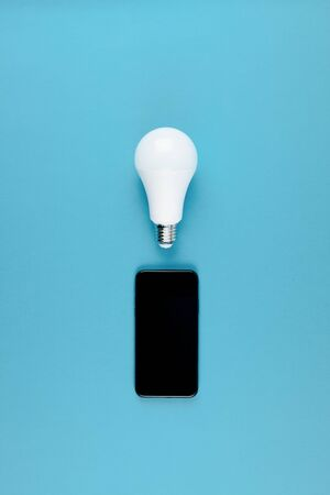 Energy-saving and eco-friendly life in conceptual frame pattern. Creative top view flat lay of LED light bulbs and modern smartphone mockup composition with copy space on blue background minimal style