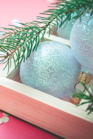 New Year Christmas Xmas holiday celebration composition pearl decorative toy balls wooden box fir branch sparkles confetti pink paper background copy space Template for greeting postcard text design