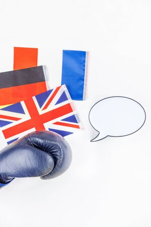 Creative top view flat lay of boxing glove with Germany France and Great Britain flags with bubble light box mock up and copy space on white background minimal style. Concept of politic fights in Europe