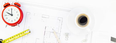 Creative flat lay overhead top view blueprint flat project plan hot coffee cup alarm clock and office supplies on decorator table workspace swatches tools and equipment background copy space concept
