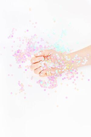 I coriandoli pastello della perla scintilla con la mano della donna su fondo bianco. Creativo concettuale vista dall'alto sfondo piatto per il tuo blog, testo o design