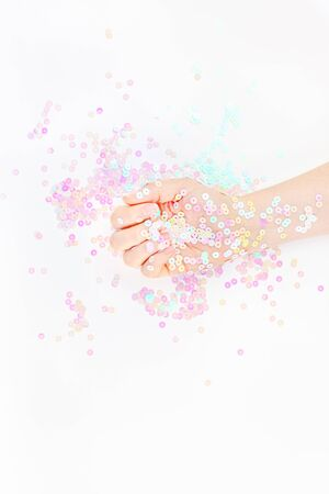 Pearl pastel confetti sparkles with woman hand on white background. Creative conceptual top view flat lay backdrop for your blog, text or design