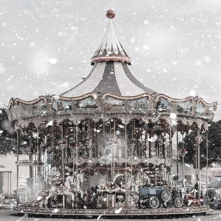Old-fashioned merry go round with horses outdoor in winter snowstorm. Pastel trendy toning. Beautiful inspiring moody faded scenery