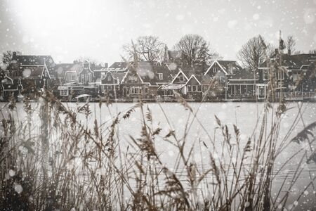 Zaanse Schans rural winter landscape with canal. Netherlands view. Pastel trendy toning. Beautiful inspiring moody faded scenery