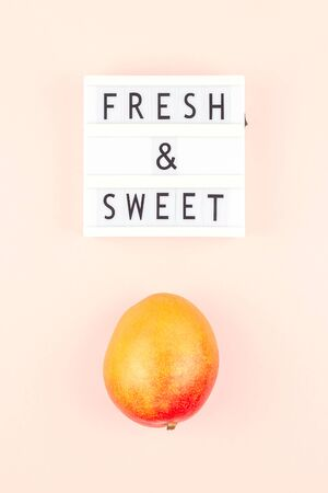 Mango fruit in creative conceptual top view flat lay composition with lightbox with Fresh and sweet text isolated on pink background in minimal style with copy space. Pop art concept poster