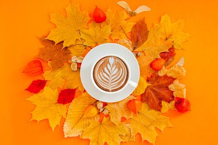 Autumn flat lay composition with dry leaves wreath frame and coffee latte cup on bold orange color background. Creative autumn, thanksgiving, fall, halloween concept. Top view, copy space