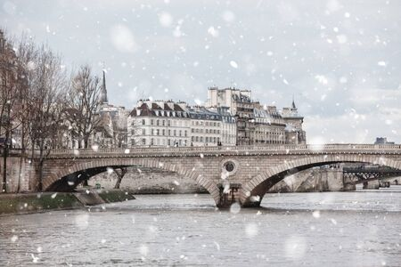 Seine River with Bridges, Paris in gloomy winter day in snowstorm. Pastel trendy toning. Beautiful inspiring moody faded scenery