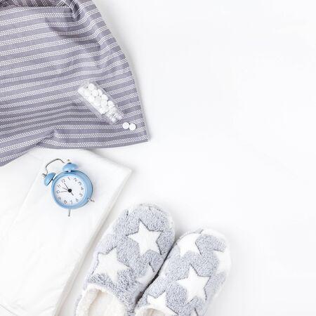 Dormire. Soffici pantofole, bottiglia con pillole e sveglia blu isolati su sfondo bianco. Vista dall'alto concettuale creativa piatta in stile minimale. Riposo, buona notte, insonnia, relax, concetto stanco