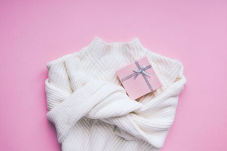 Creative valentines day romantic flat lay overhead top view white sweater and gift box on pink background copy space minimal style with natural light. 14 February holiday template for feminine blog