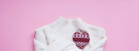 Creative valentines day romantic flat lay overhead top view white sweater and knitted heart pink background copy space minimal style with natural light. 14 February holiday template for feminine blog