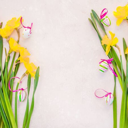 Creative flat lay top view Easter eggs greeting card with yellow daffodils flowers on pink background. Celebration Postcard template
