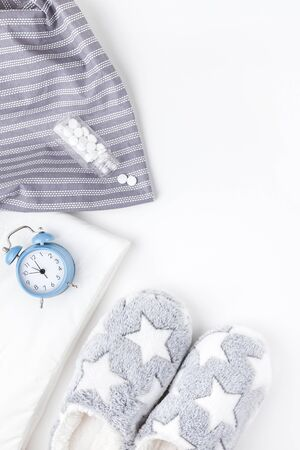 Sleep. Fluffy slippers, bottle with pills and blue alarm clock isolated on white background. Creative conceptual top view flat lay minimal style. Rest, good night, insomnia, relaxation, tired concept