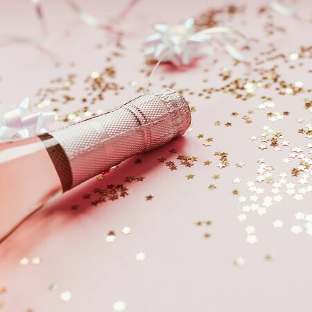 Christmas or New Year composition with bottles of rose champagne and golden shiny sparkle star confetti on pastel pink background, side view. Party Celebration creative concept